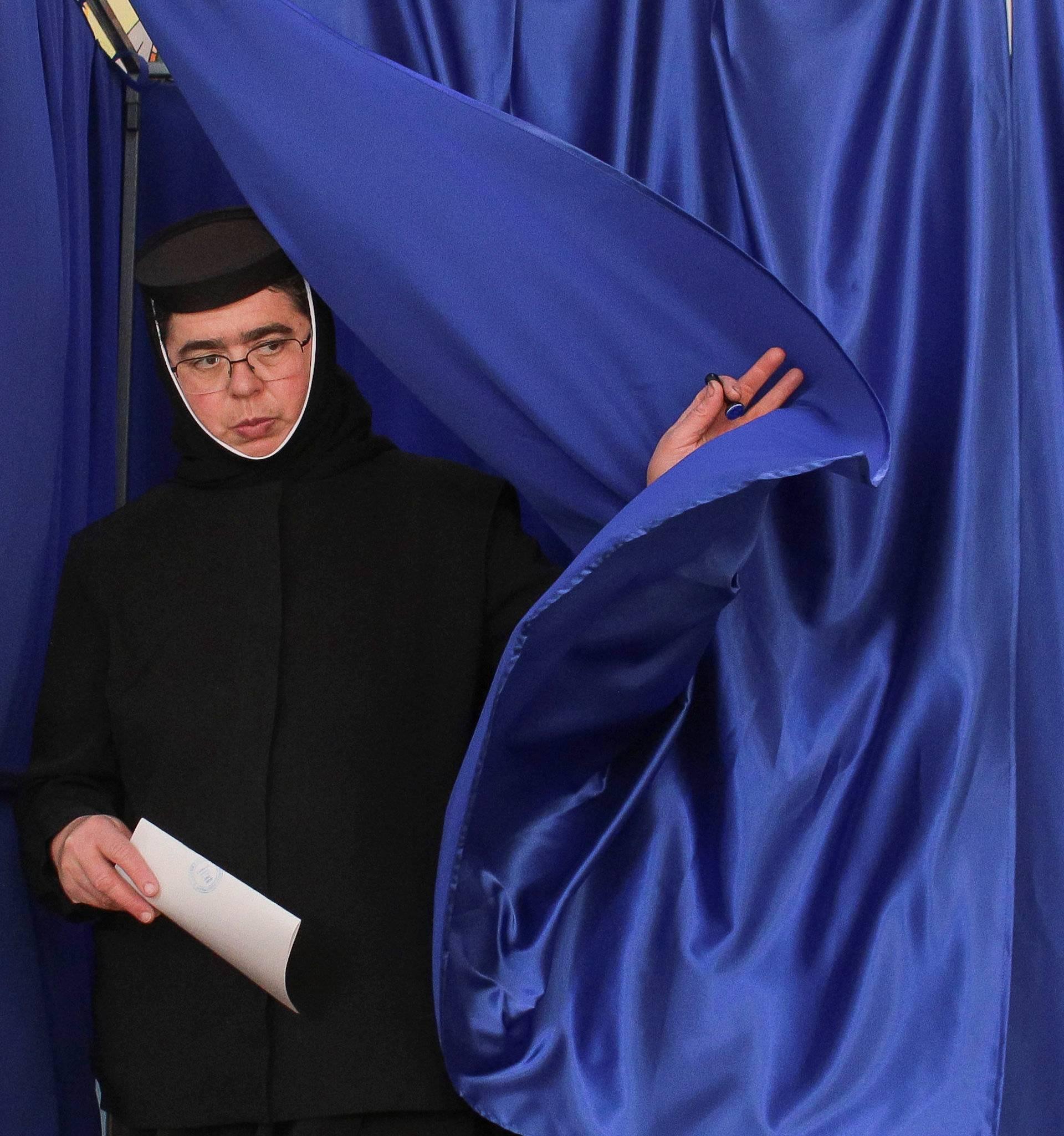 A nun exits a voting booth in Ciorogarla