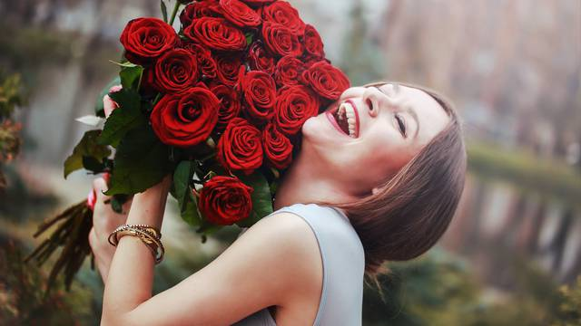 beautiful young woman with a large bouquet of flowers in the park
