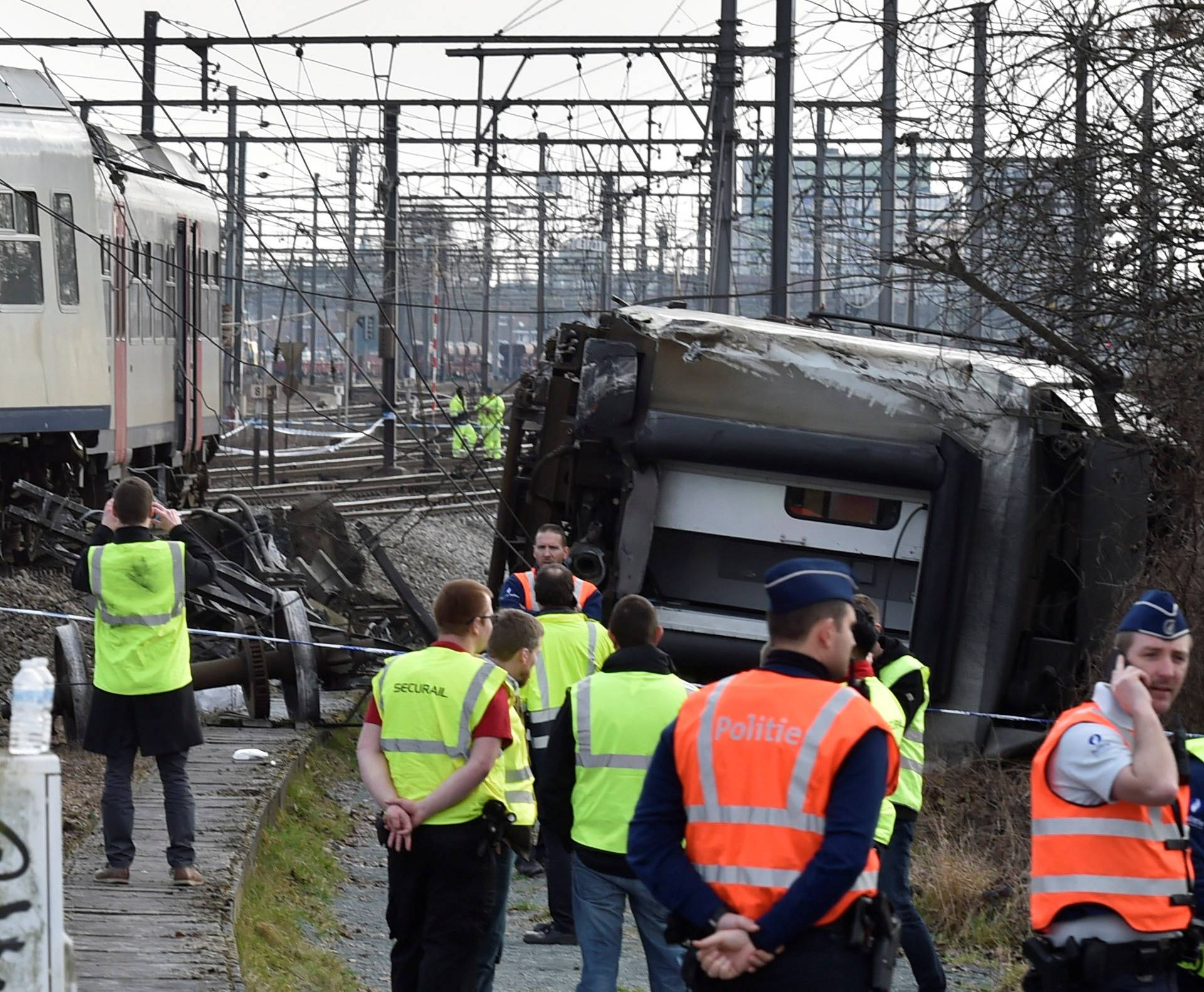 Rescuers and police officers stand next to the wreckage of a passenger train after it derailed in Kessel-Lo near Leuven