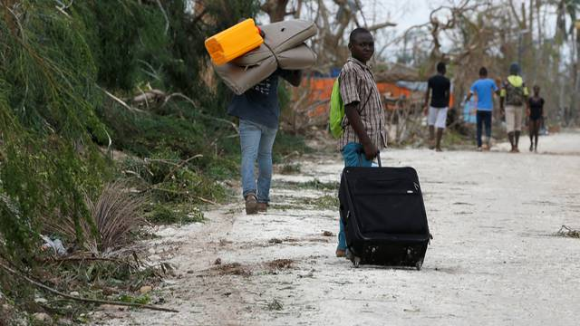 People carry their belongings on the street after Hurricane Matthew passes Jeremie