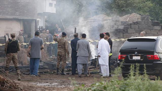 Pakistan soldiers and officers survey the site after a military aircraft on a training flight crashed in a built-up area in the garrison city of Rawalpindi,