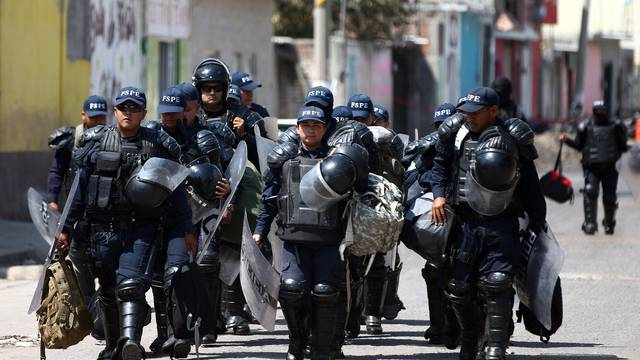 Police officers patrol a street after a blockade set by members of the Santa Rosa de Lima Cartel to repel security forces during an anti-fuel theft operation in Santa Rosa de Lima