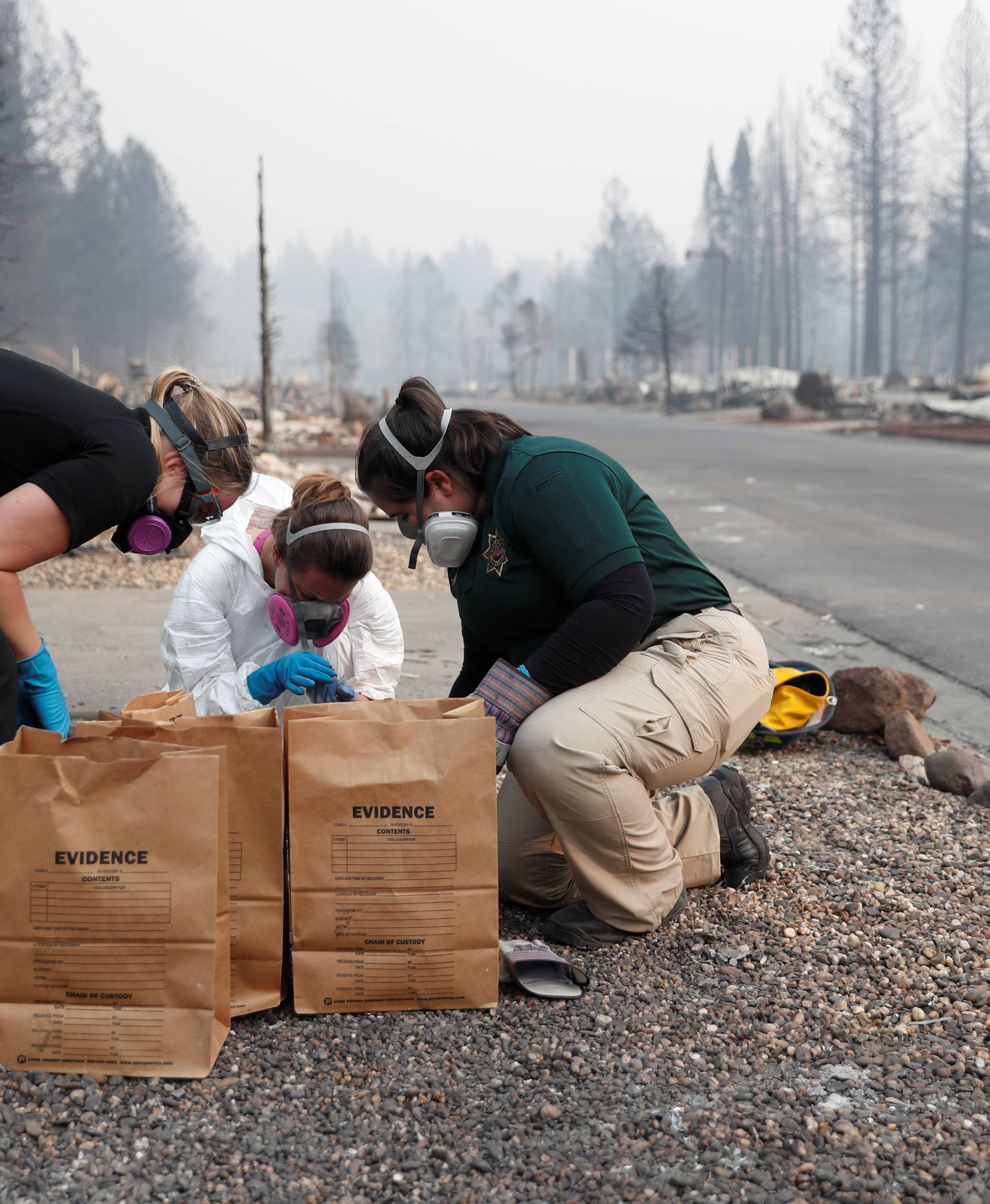 Forensic anthropologist Kyra Stull (C) works with coroners to recover human remains from a trailer home destroyed by the Camp Fire in Paradise