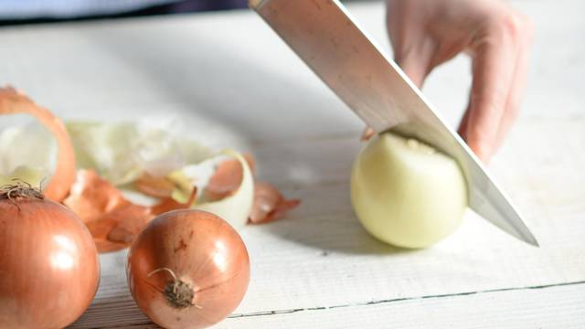 Woman hand cut fresh onion on white table