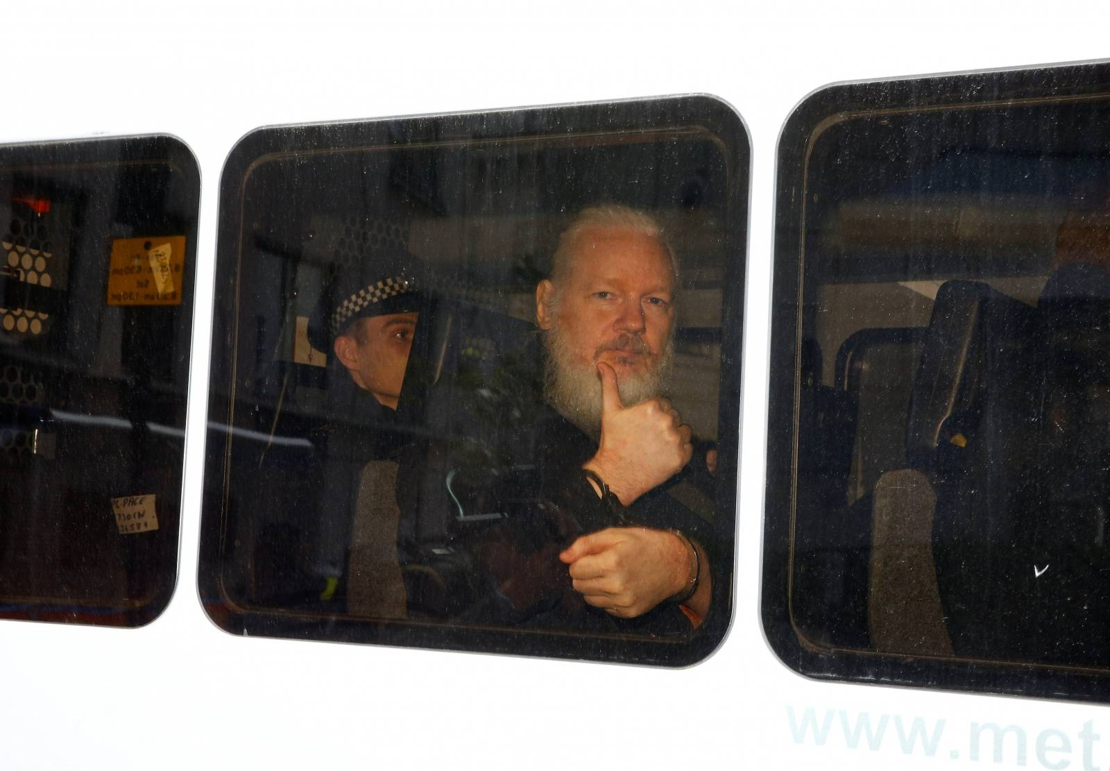 WikiLeaks founder Julian Assange is seen in a police van after was arrested by British police outside the Ecuadorian embassy in London