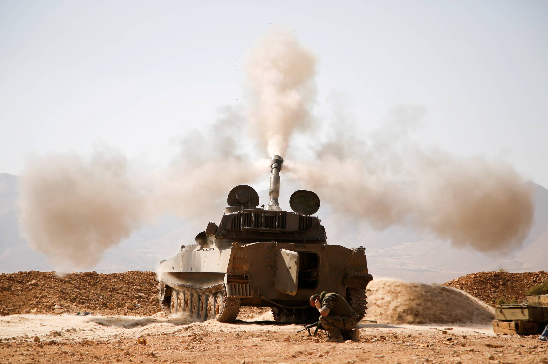 FILE PHOTO: A Hezbollah fighter reacts as he fires a weapon in Western Qalamoun
