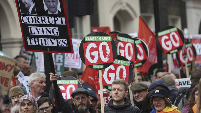 Demonstrators hold placards during an anti-austerity protest in London