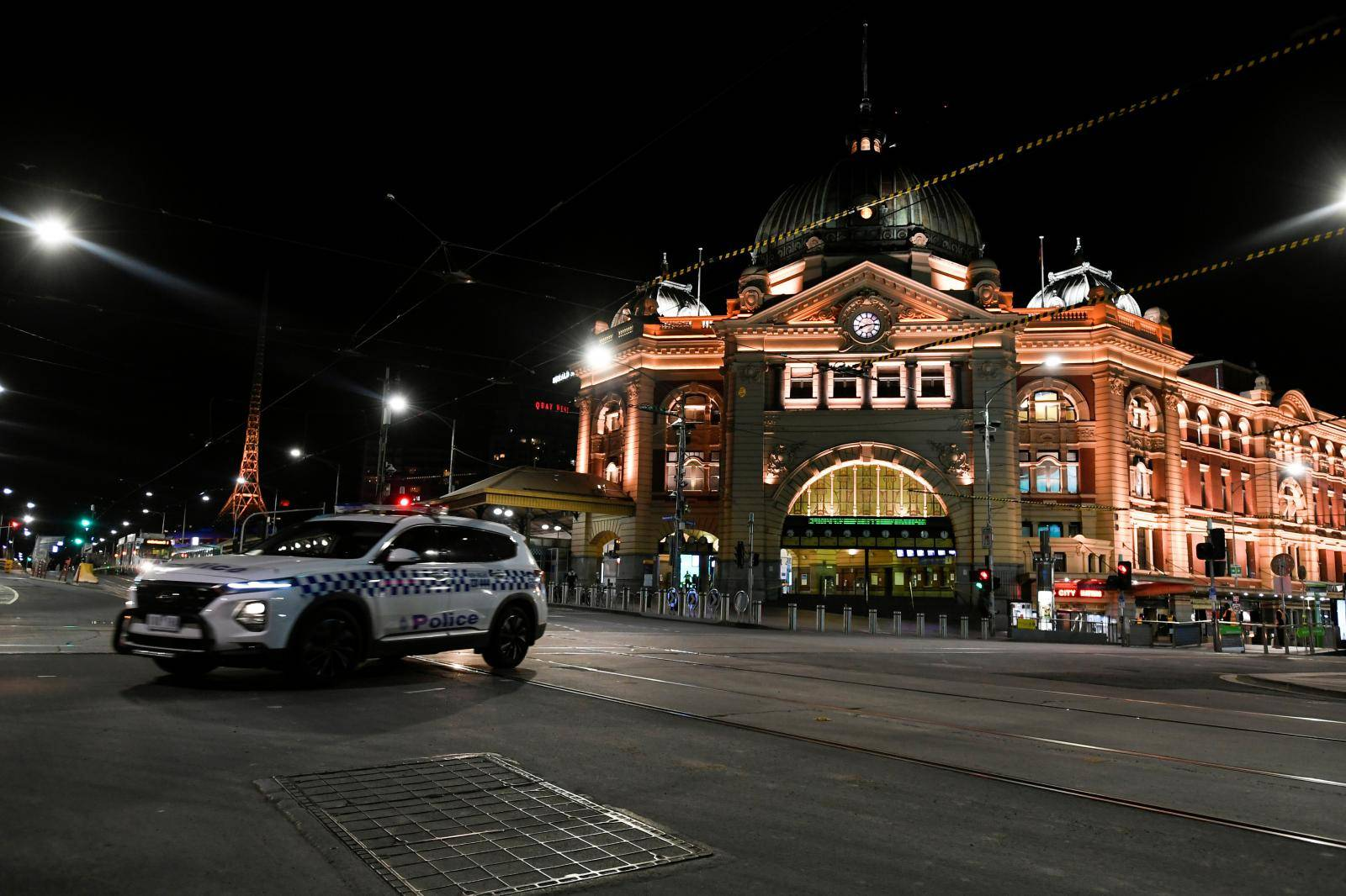 A police car is seen outside a transit hub after a citywide curfew was introduced to slow the spread of COVID-19 in Melbourne