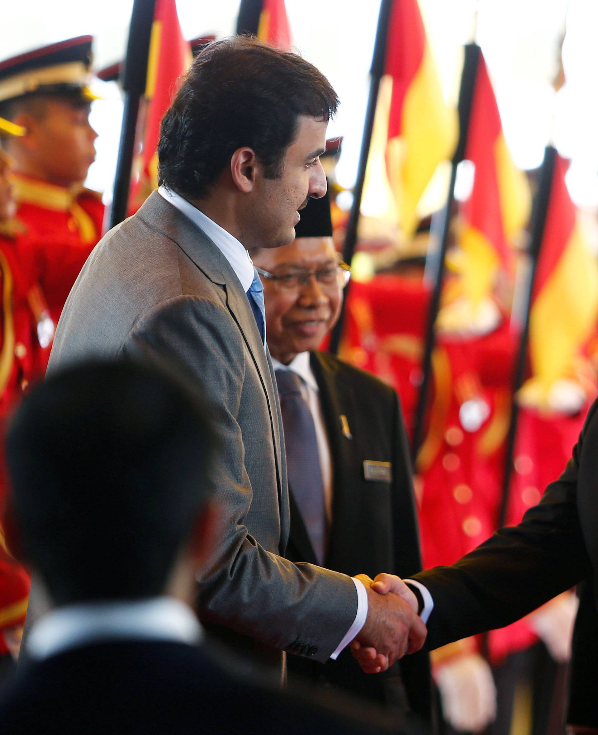FILE PHOTO: Qatar's Emir Sheikh Tamim bin Hamad al-Thani shakes hand with Malaysia's King Muhammad V after a state welcome ceremony at the Parliament House in Kuala Lumpur