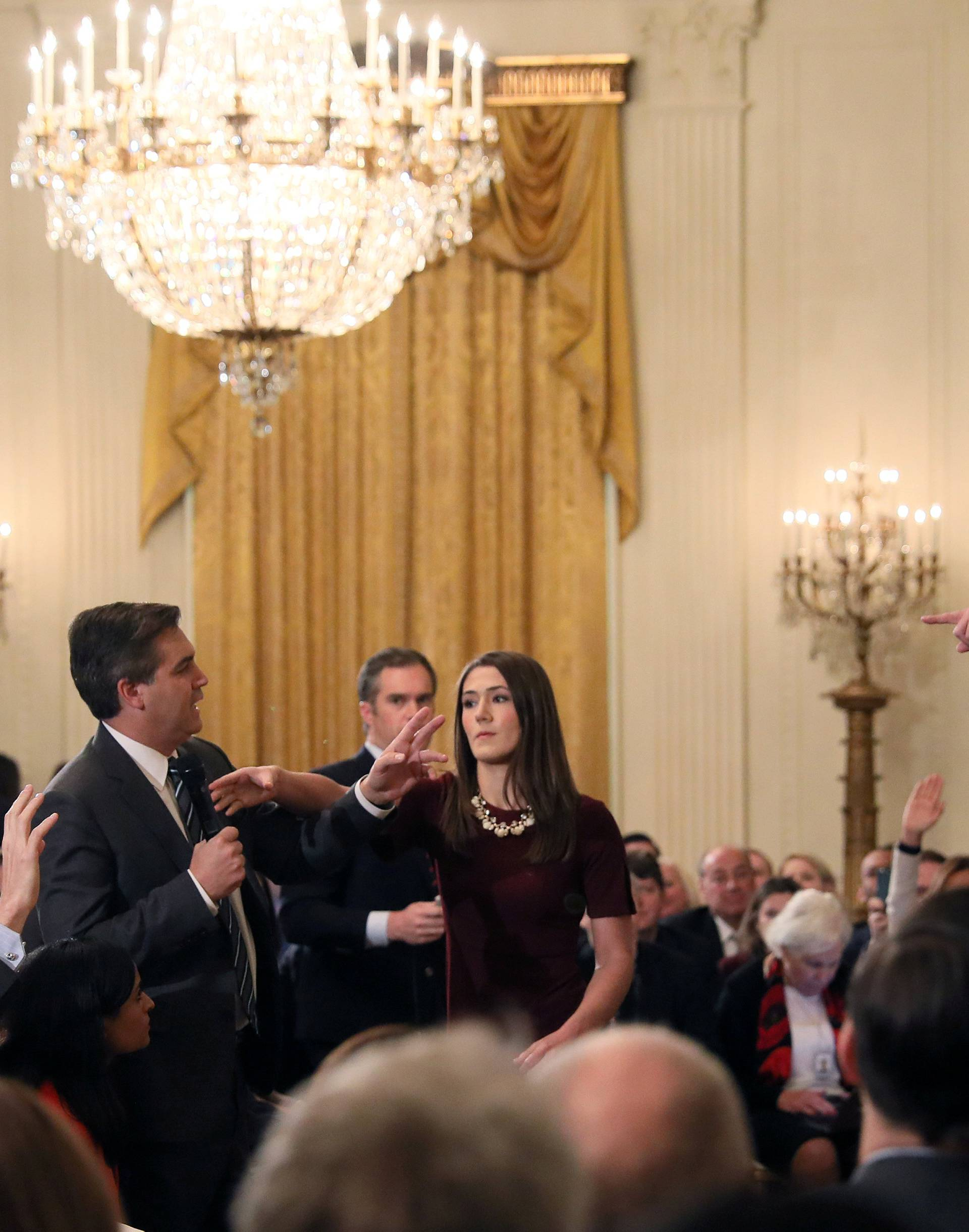 A White House staff member reaches for the microphone held by CNN's Jim Acosta as he questions U.S. President Donald Trump during a news conference in Washington