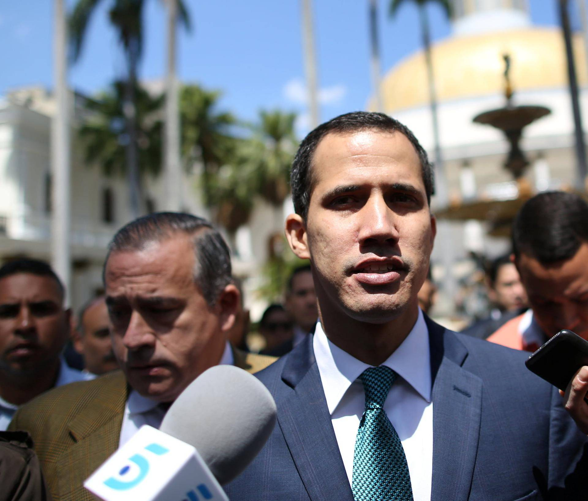 Venezuelan opposition leader Juan Guaido walks as he speaks to journalists before a news conference at the National Assembly in Caracas