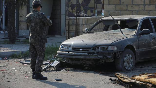 FILE PHOTO: A man stands in front of a damaged car following shelling in Barda