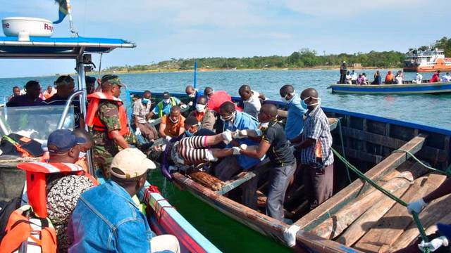 Rescue workers retrieve a body of a woman from the water after a ferry overturned off the shores of Ukerewe Island on Lake Victoria