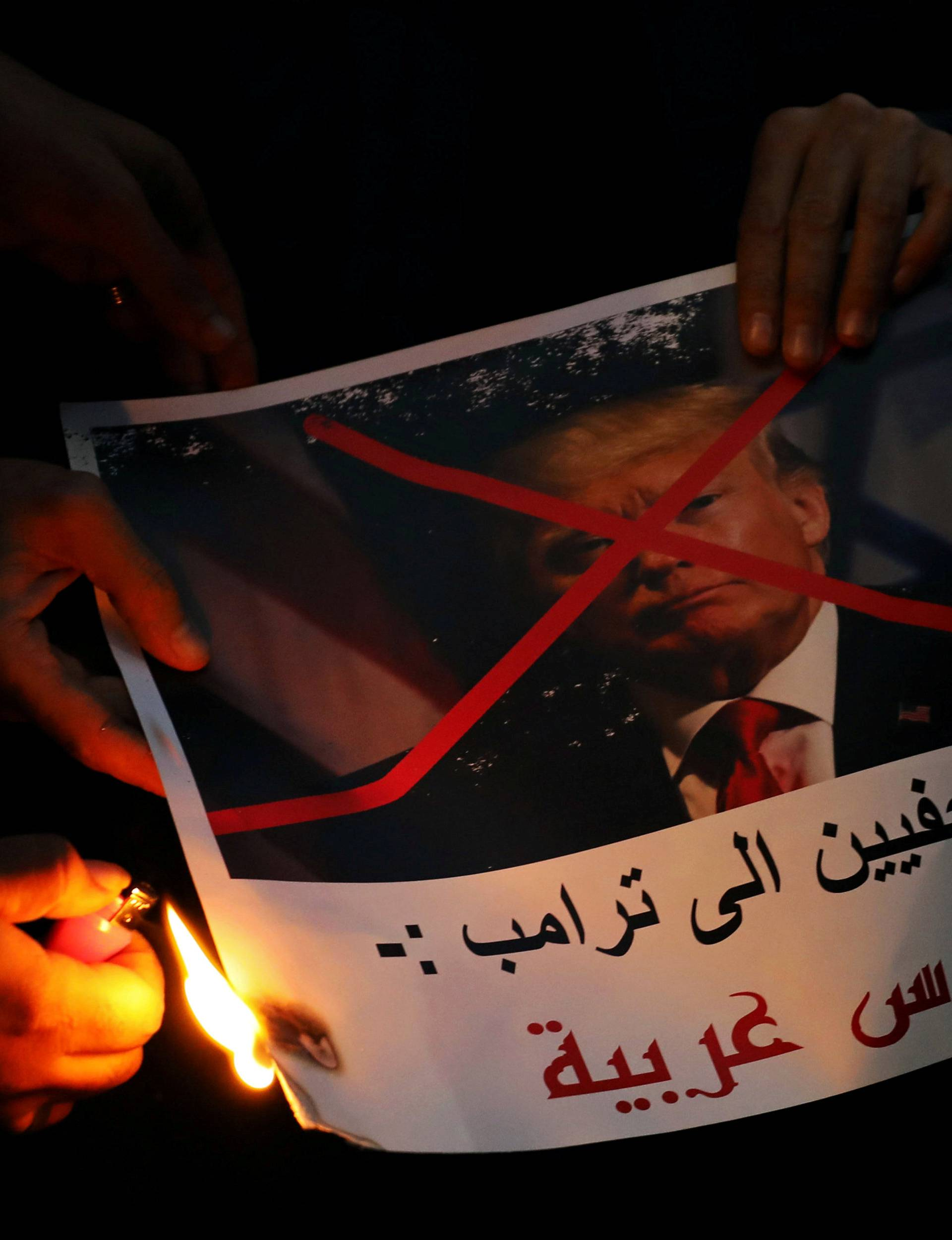 """People burn a poster of Trump reading """"Journalists are telling you Trump, Jerusalem is Arab"""" during a protest against Trump's Jerusalem declaration, in front of the Syndicate of Journalists in Cairo"""