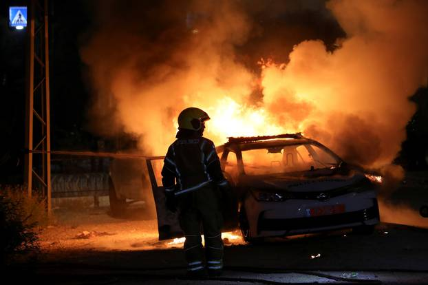 An Israeli firefighter stands near a burning Israeli police car during clashes between Israeli police and members of the country