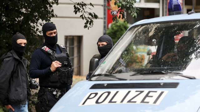 Police officers gather outside during a raid in an apartment building at Kreuzberg district in Berlin