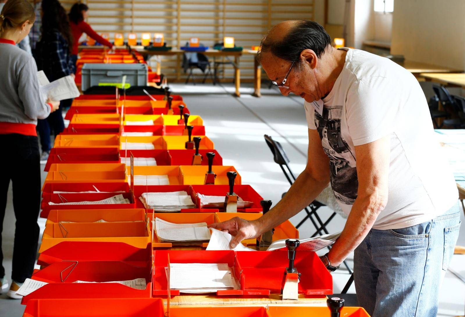 Member of the district election office Stadtkreis 3 sorts ballots for the Swiss federal elections in Zurich
