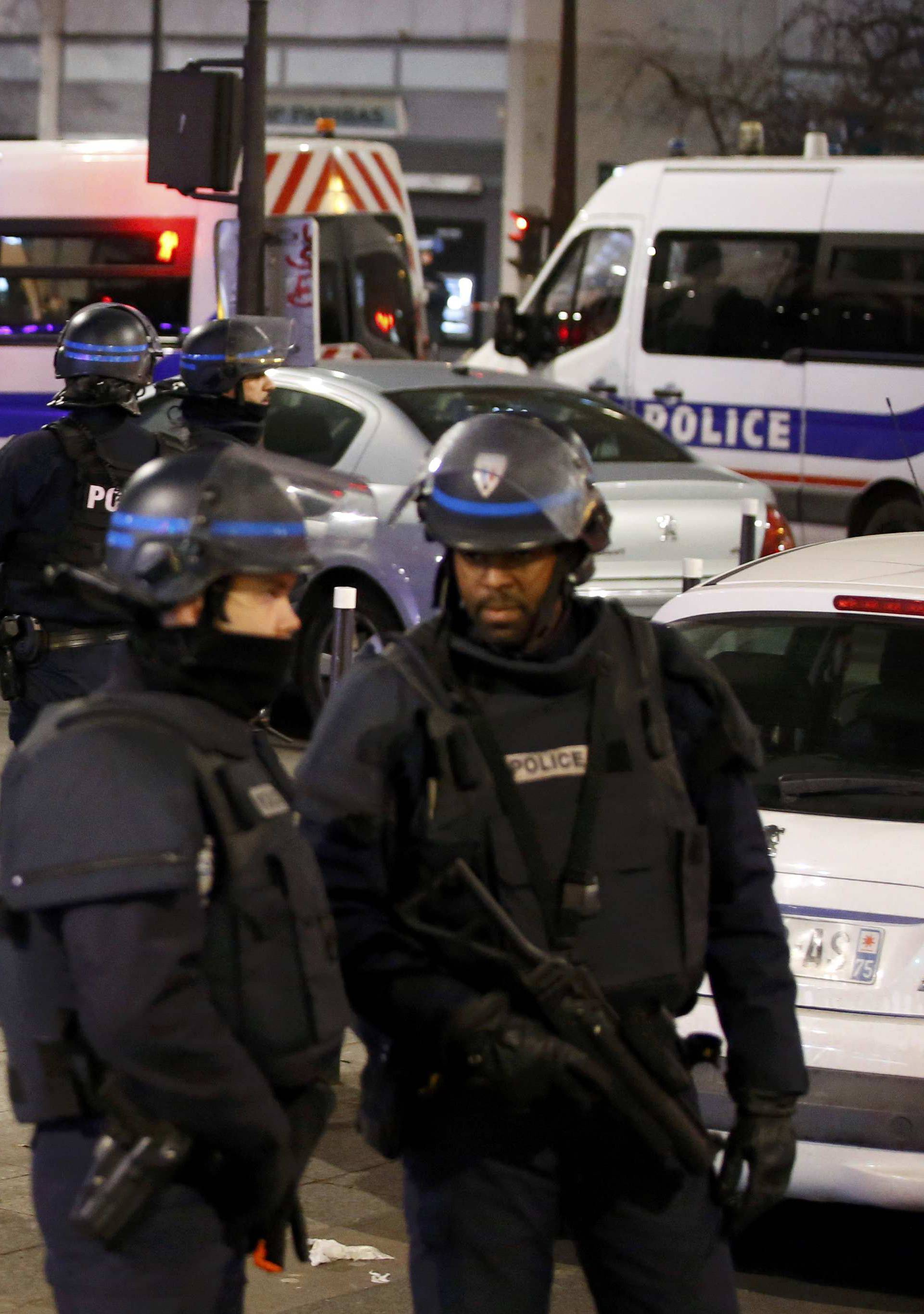 French police secure a street near the travel agency where a gunman has taken hostage about half a dozen people in what appears to be a robbery, a police source said, in Paris