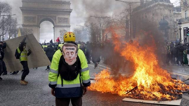 """A demonstrator stands near a burning barricade during a demonstration by """"yellow vests"""" in Paris"""