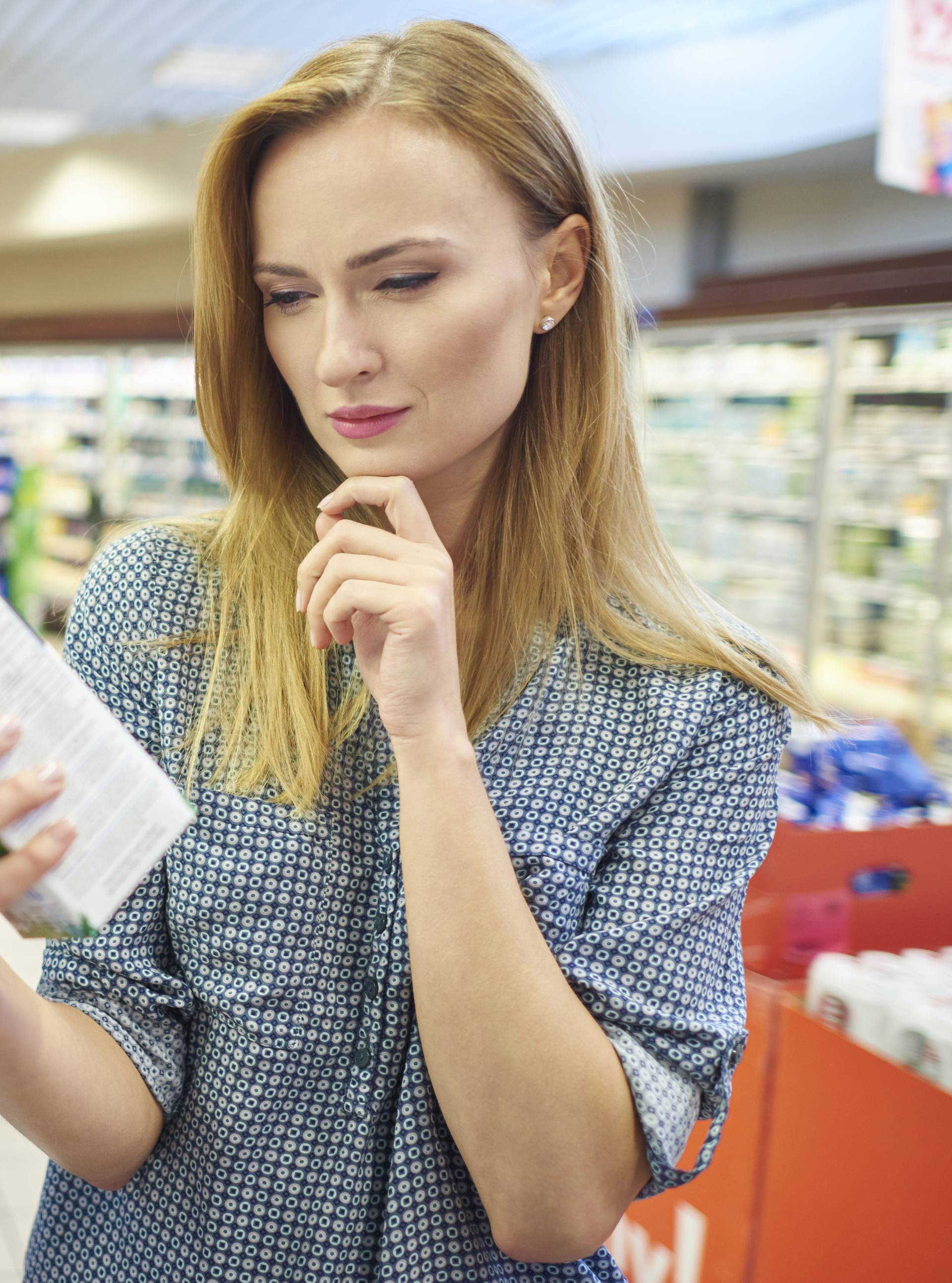 Young woman reading label milk