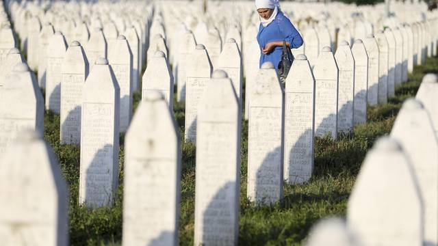 A woman walks among graves in Memorial Center Potocari, near Srebrenica