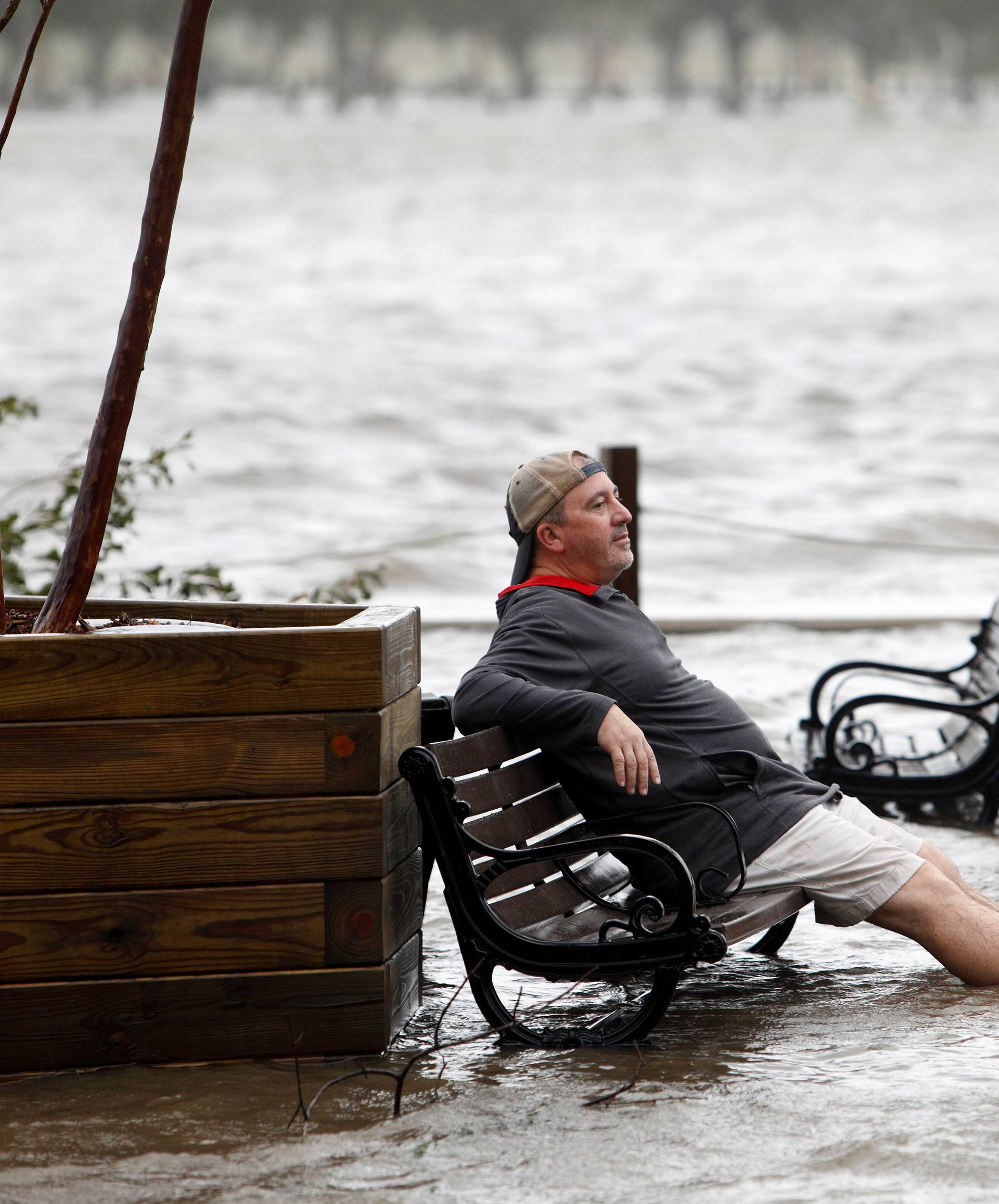 A man sits on a park bench in a flooded park as the Cape Fear River rises above its usual height in Wilmington, North Carolina