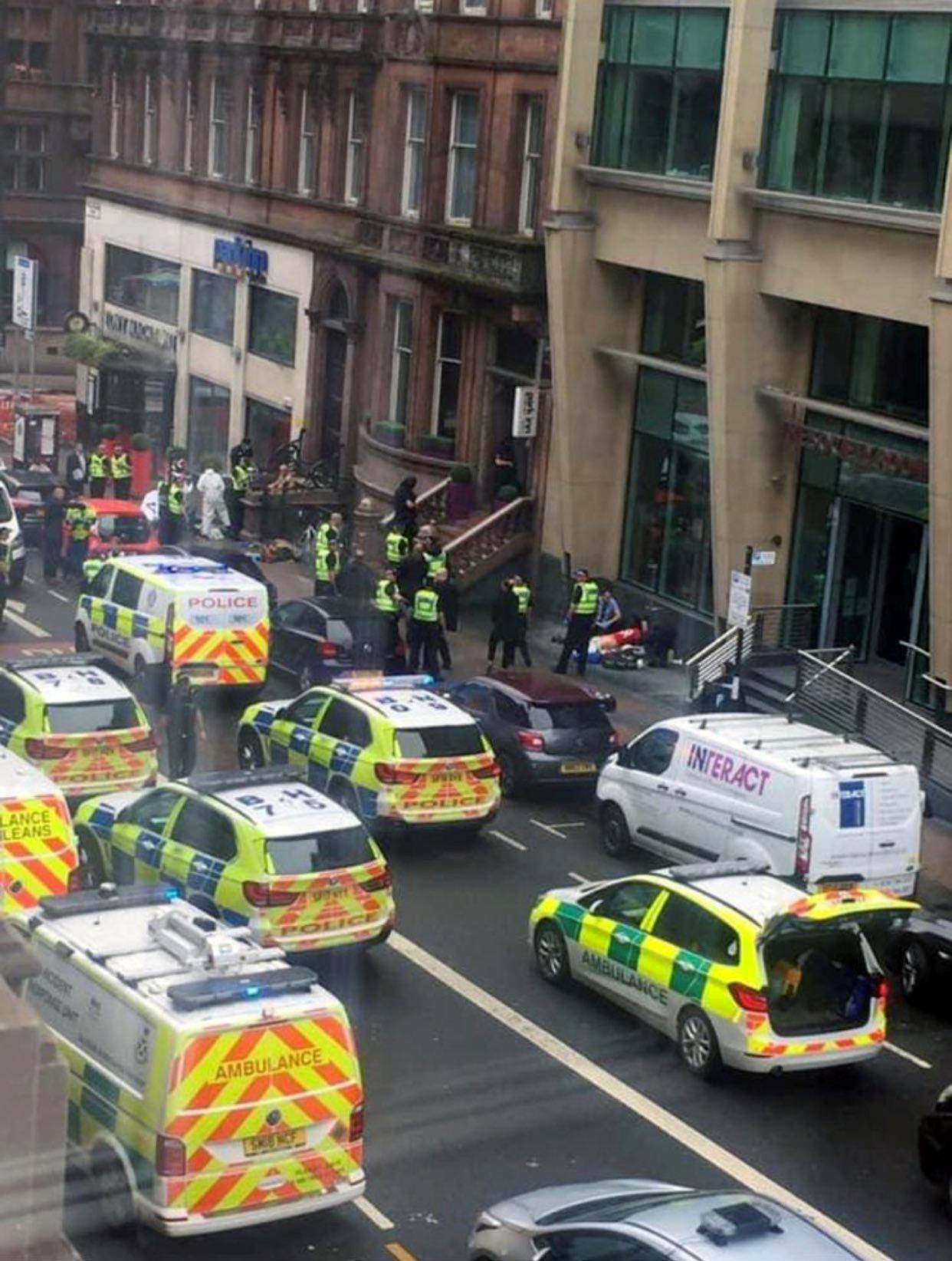 Police officers and emergency responders are seen at the scene of reported stabbings, in Glasgow