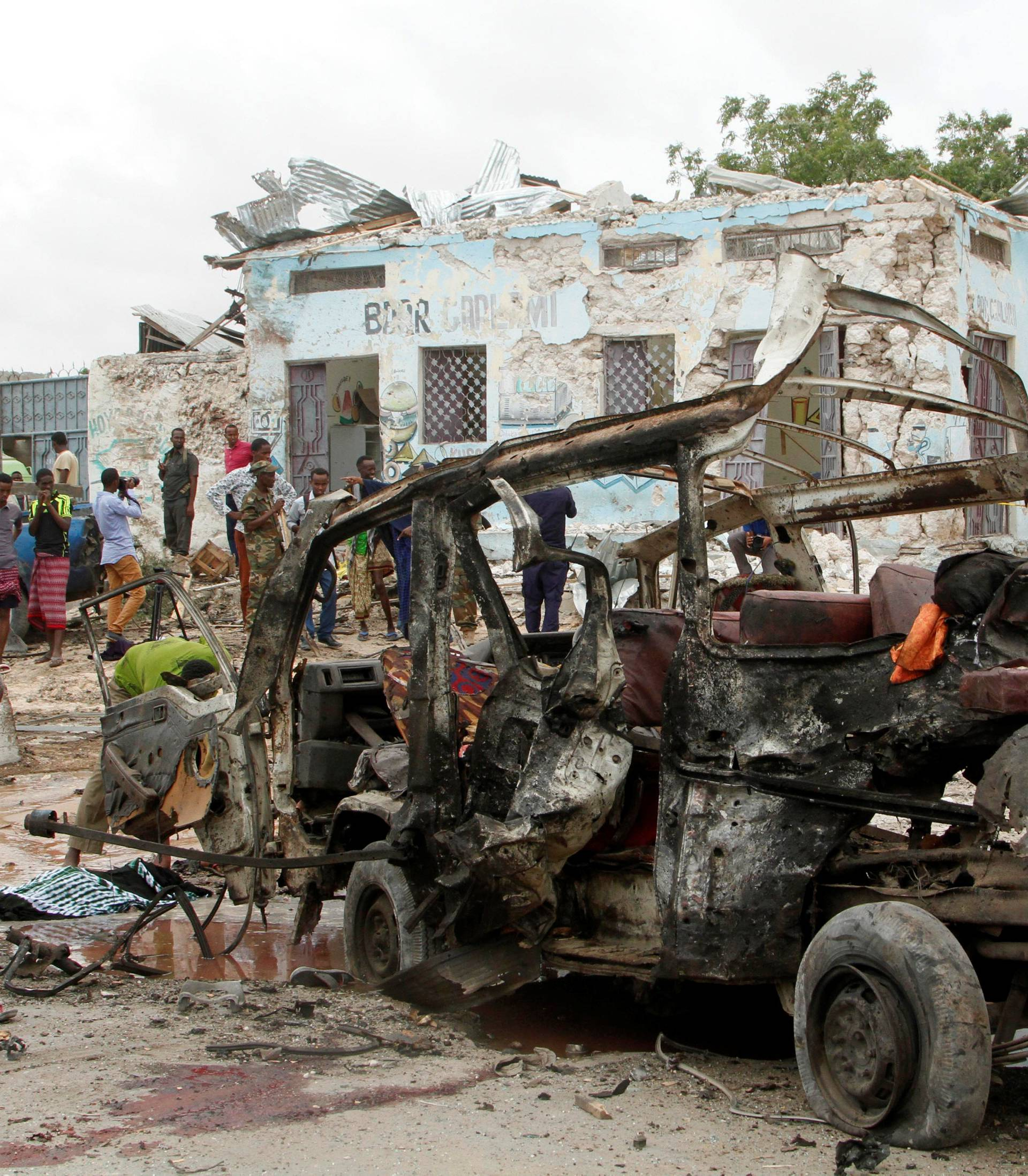Civilians remove the body of an unidentified man from the wreckage of a minibus at the scene of an explosion near  a military base in Somalia's capital Mogadishu
