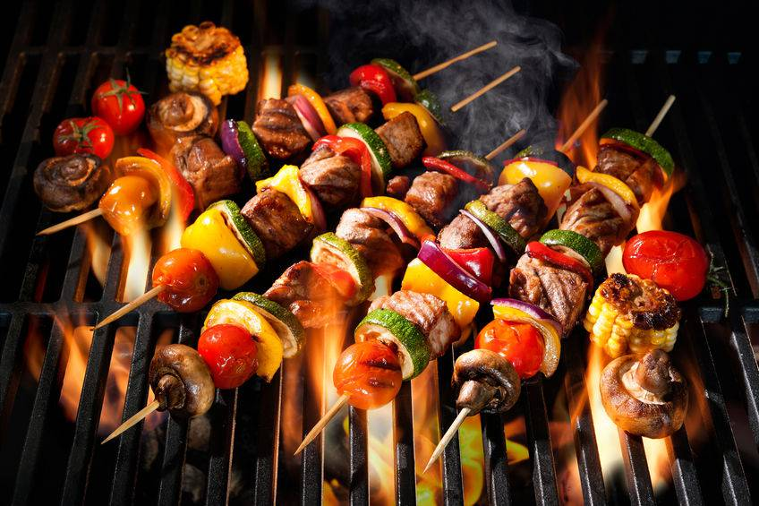 Meat kebabs with vegetables on flaming grill