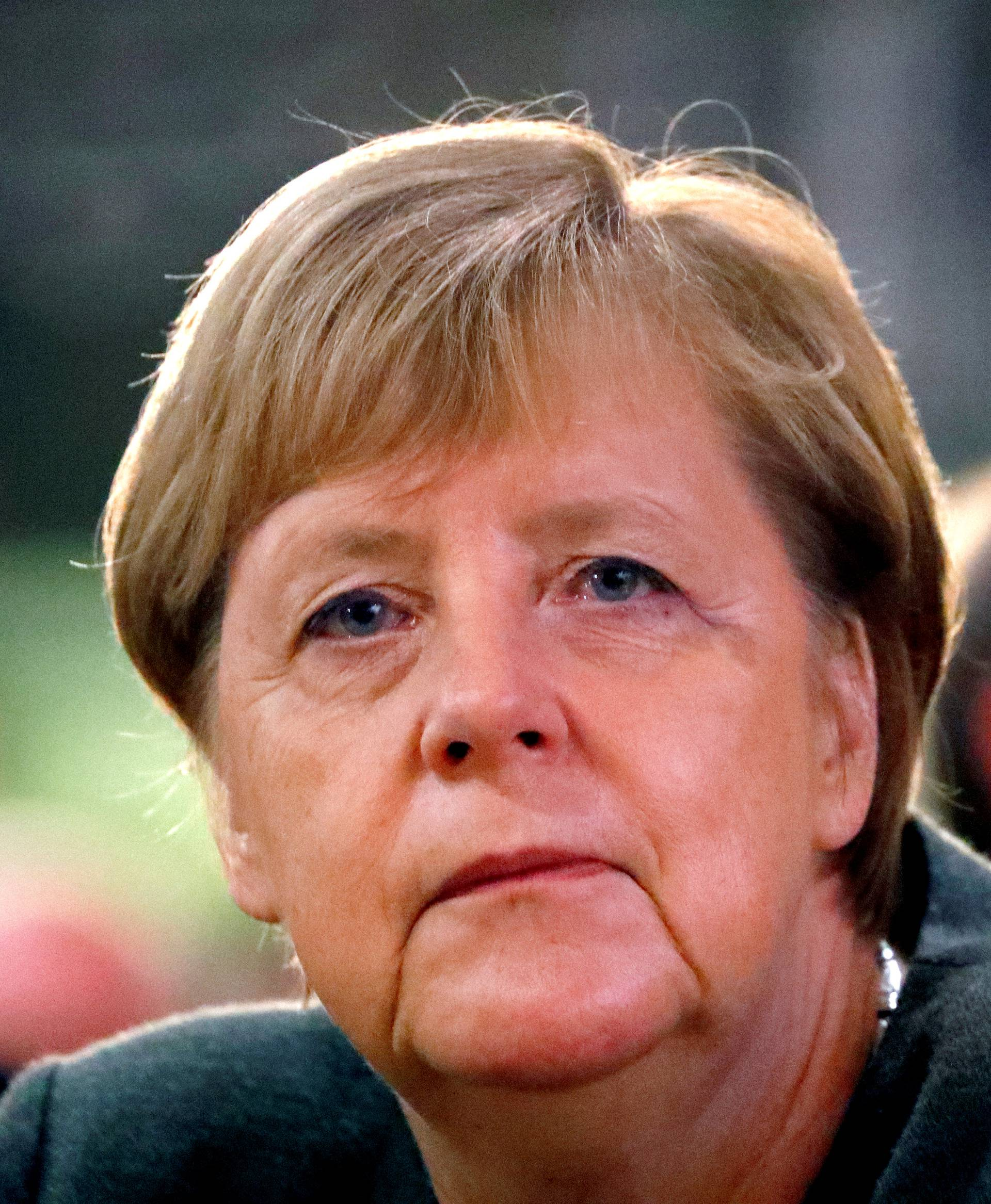 FILE PHOTO: German Chancellor Angela Merkel listens to Hesse State Prime Minister Volker Bouffier's speech during his election campaign rally in Ortenberg