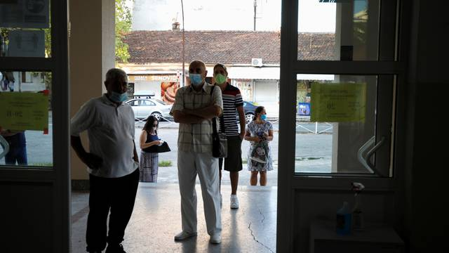 Voters wearing face masks due to the ongoing coronavirus disease (COVID-19) outbreak wait for the opening of a polling station during the general election in Podgorica