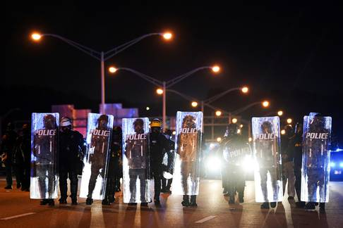 Police with riot shields advance to detain protesters for blocking traffic on a freeway during a rally against racial inequality and the police shooting death of Rayshard Brooks, in Atlanta