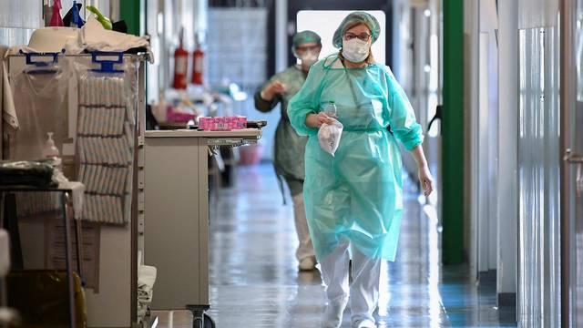 Medical workers wearing protective masks and suits walk in an intensive care unit at the Oglio Po hospital in Cremona