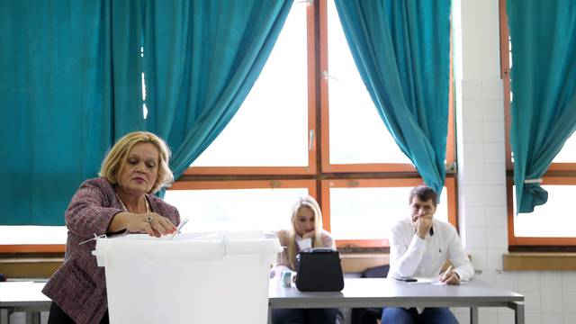 A woman casts her ballot during presidential and parliamentary elections at a polling centre in a school in Babino near Zenica