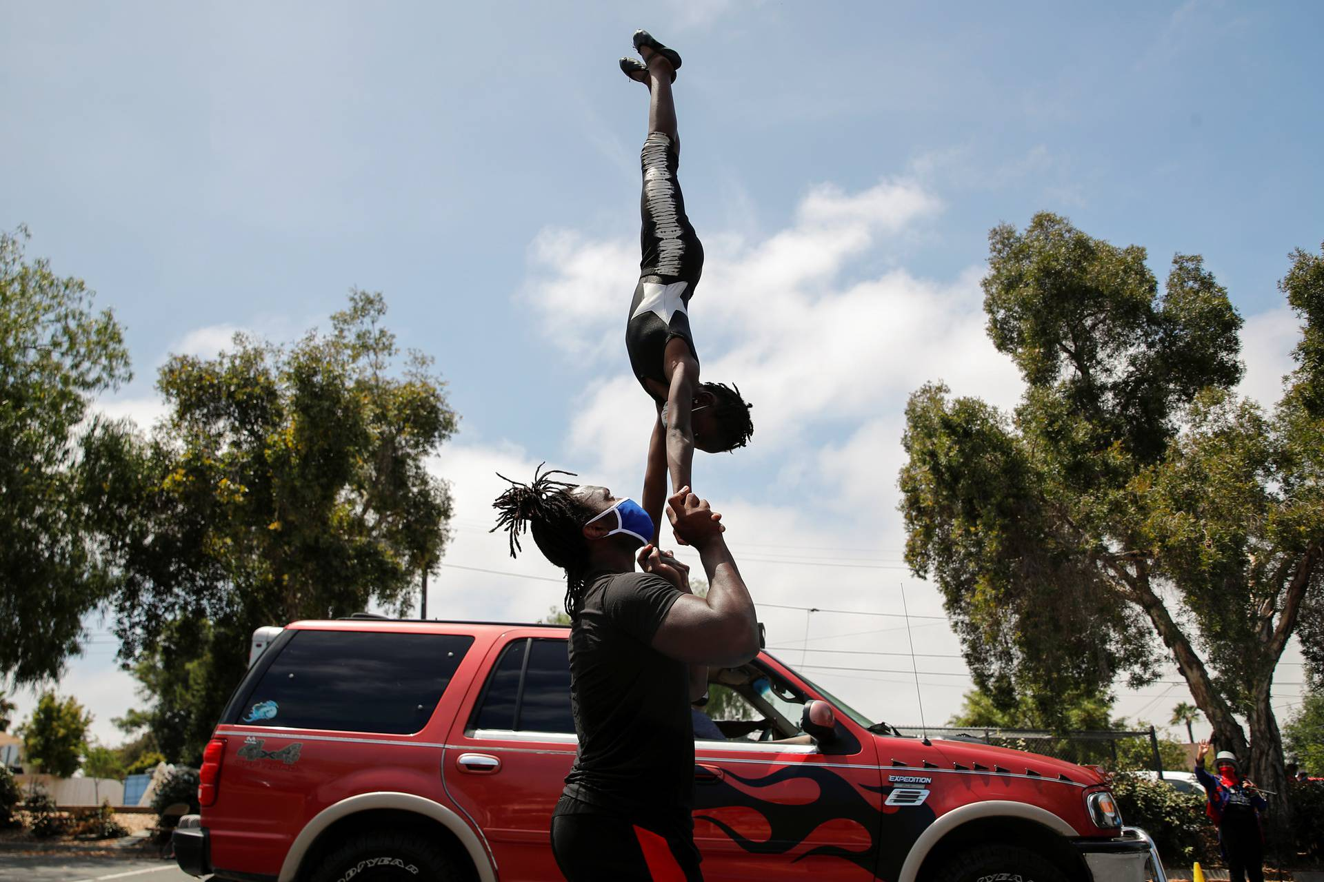 Circus performers intertain kids and parents in food bank drive therough line in San Diego