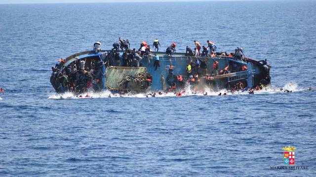 """Migrants are seen on a capsizing boat before a rescue operation by Italian navy ships """"Bettica"""" and """"Bergamini"""" (unseen) off the coast of Libya"""