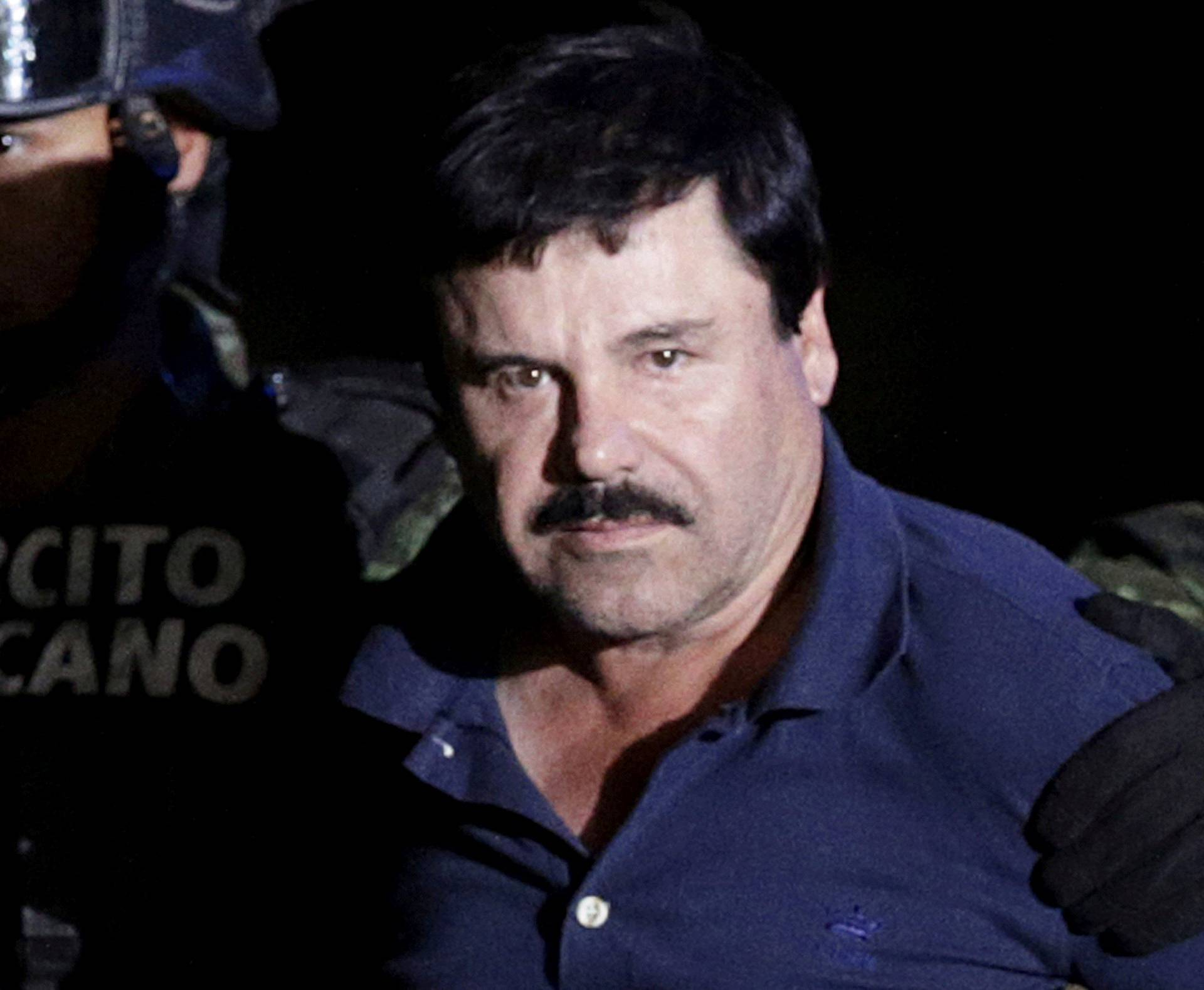 "FILE PHOTO: Recaptured drug lord Joaquin ""El Chapo"" Guzman is escorted by soldiers at the hangar belonging to the office of the Attorney General in Mexico City"