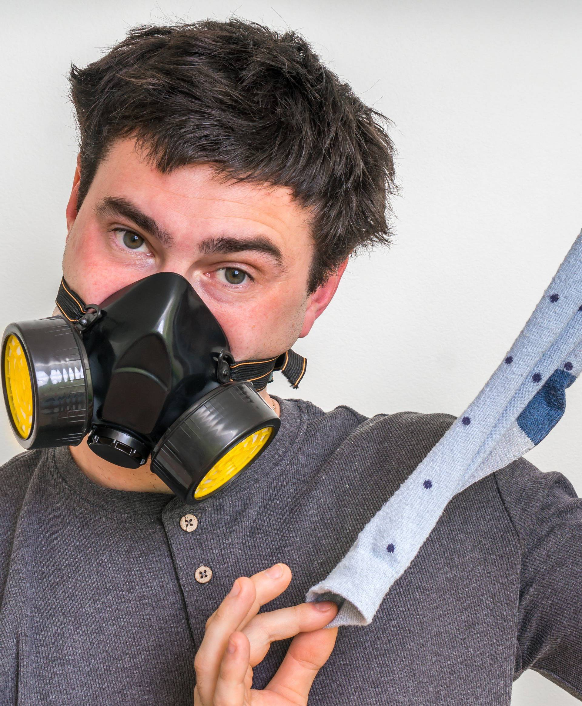Man with gas mask is holding dirty stinky sock