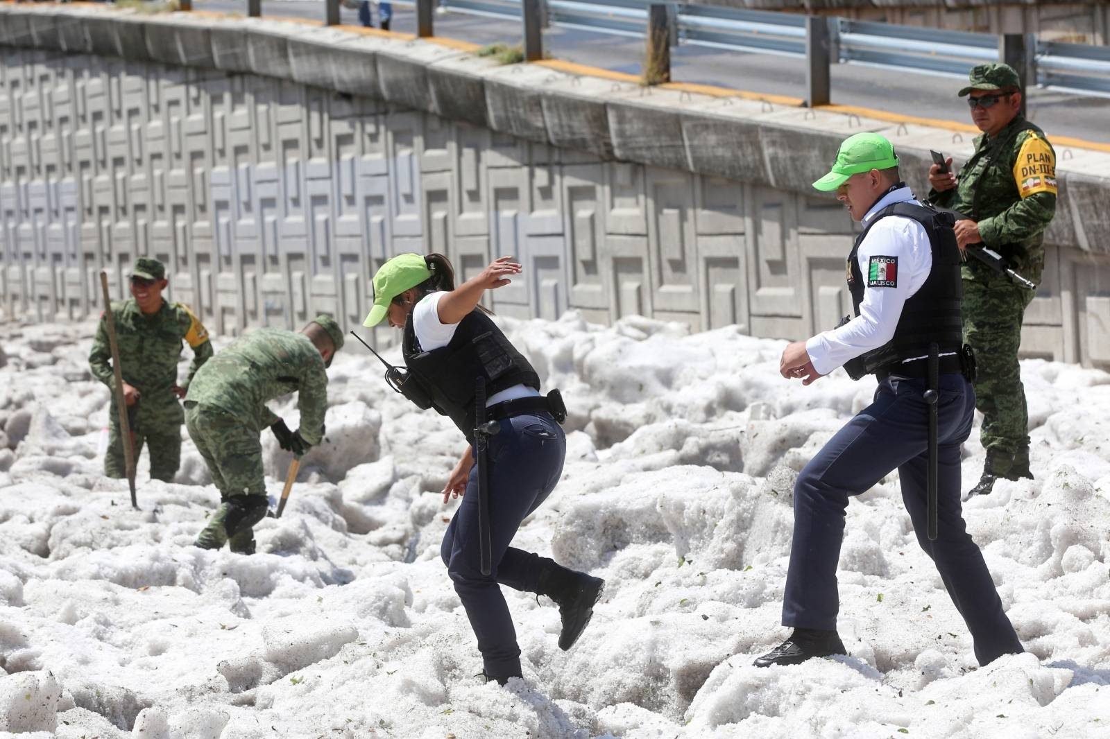 Security forces and soldiers try to clear away ice after a heavy storm of rain and hail which affected some areas of the city in Guadalajara