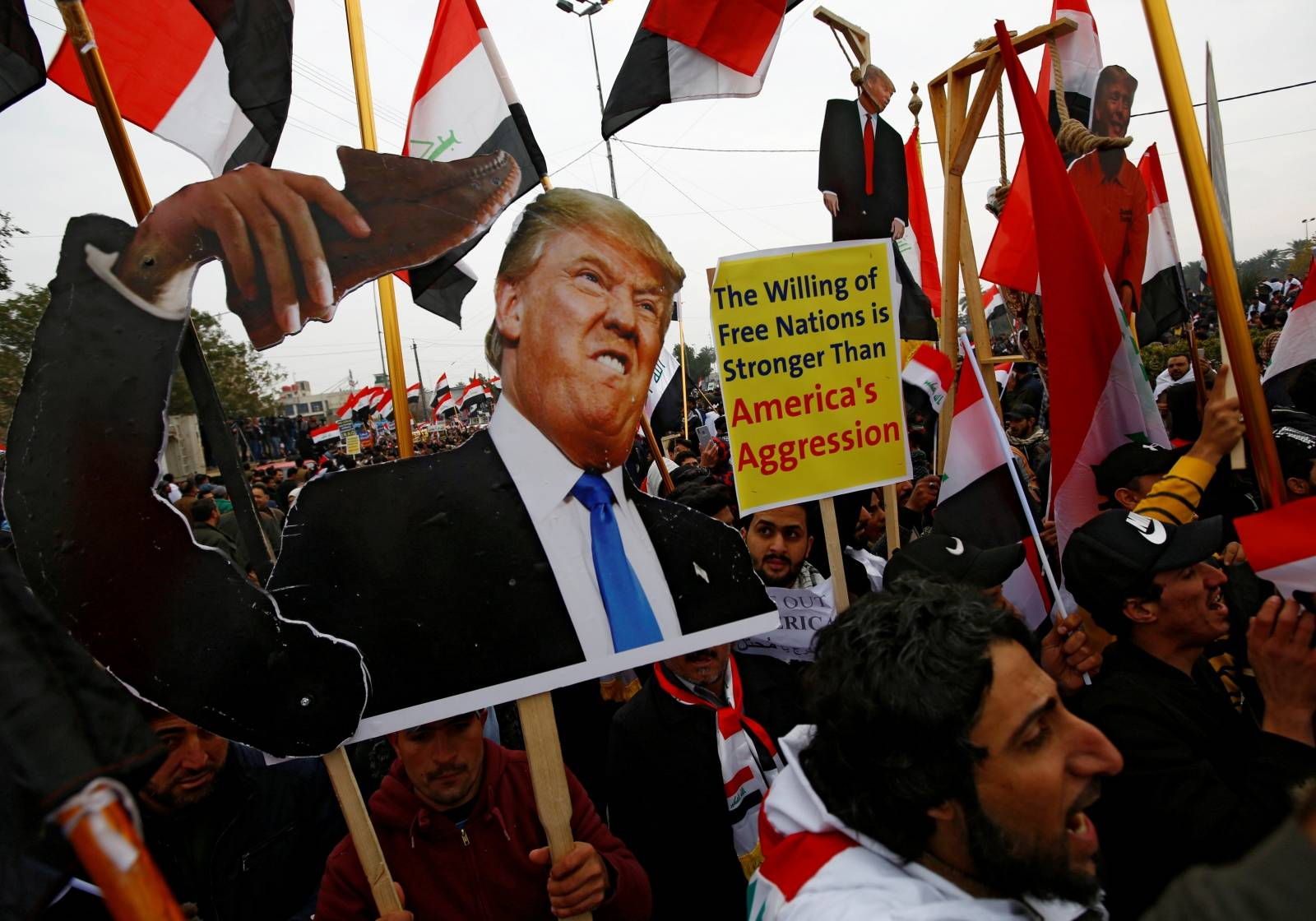 Supporters of Iraqi Shi'ite cleric Moqtada al-Sadr carry placards depicting U.S. President Donald Trump at a protest against what they say is U.S. presence and violations in Iraq, duri in Baghdad
