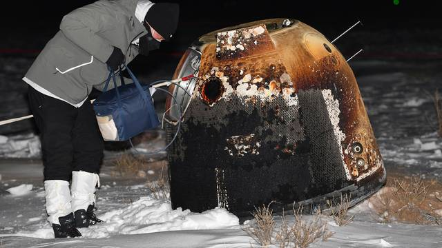 Researcher works next to Chang'e-5 lunar return capsule carrying moon samples after it landed in northern China's Inner Mongolia Autonomous Region