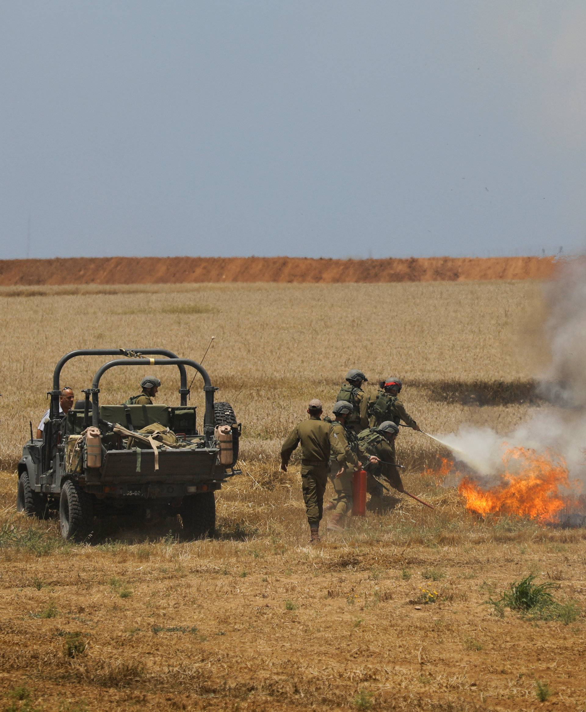 Israeli soldiers attempt to extinguish a fire in a field on the Israeli side of the border fence between Israel and Gaza near kibbutz Mefalsim