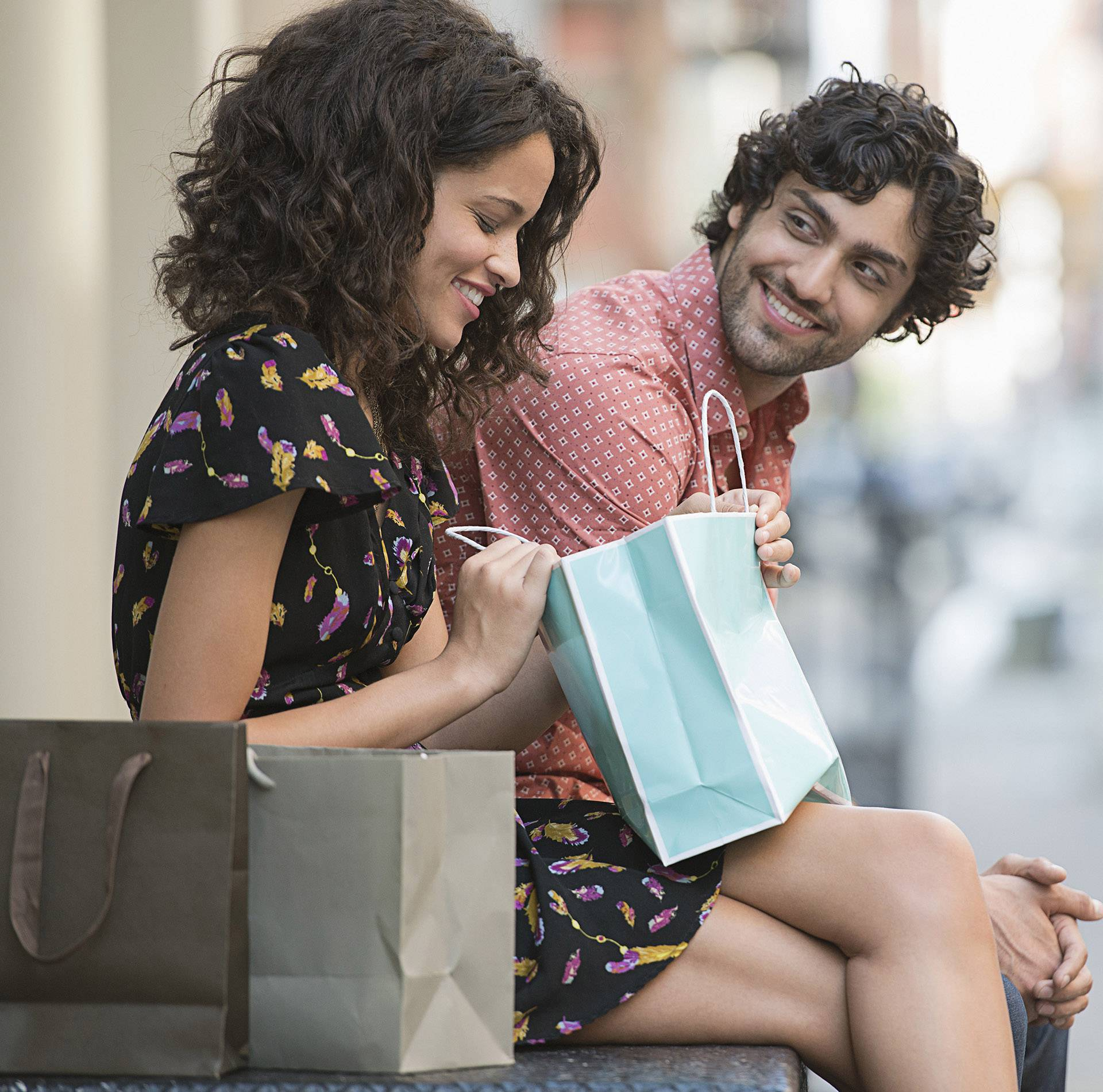 Young happy couple sitting outdoors during break in shopping