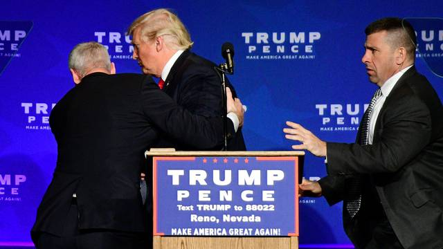 Donald Trump is hustled off the stage by security agents in Reno