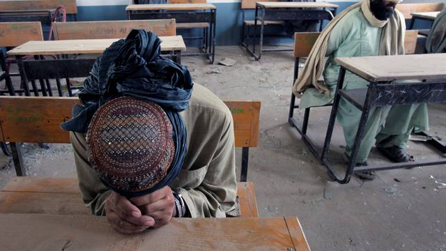 FILE PHOTO: A group of men detained for suspected Taliban activities are held for questioning at a schoolhouse in the village of Kuhak