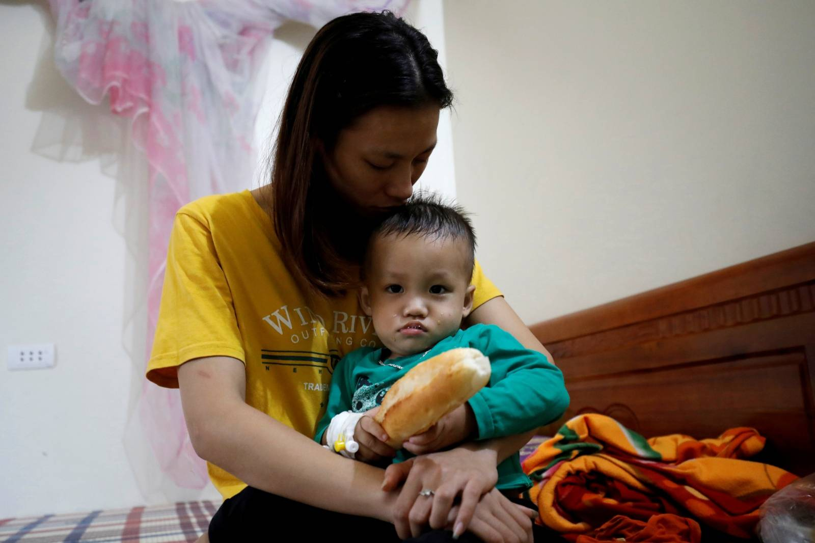 Hoang Thi Thuong, wife of Nguyen Dinh Tu, a Vietnamese suspected to be among dead victims found in a lorry in Britain, holds her son Nguyen Dinh Dan at their home in Nghe An province