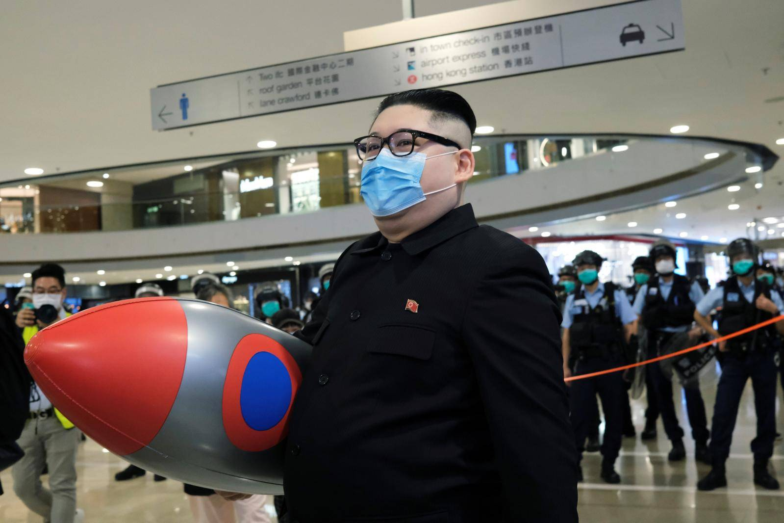 Howard X, an Australian-Chinese impersonating North Korean leader Kim Jong-un walks near riot police as officers clear the crowd in a mall to avoid the spread of the coronavirus disease (COVID-19) during an anti-government protest in Hong Kong