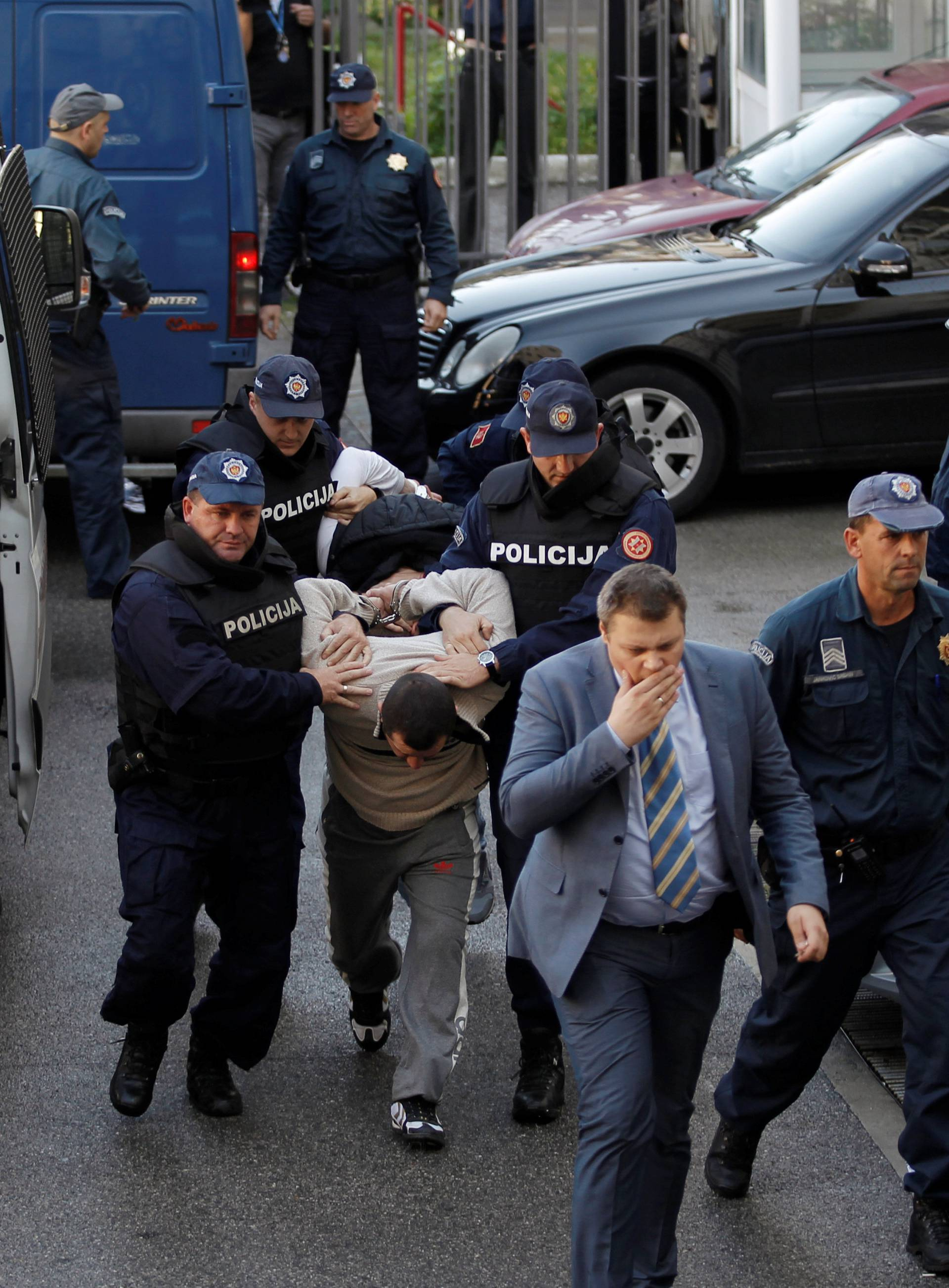 Montenegrin police escort men to a court session with the state attorney in Podgorica