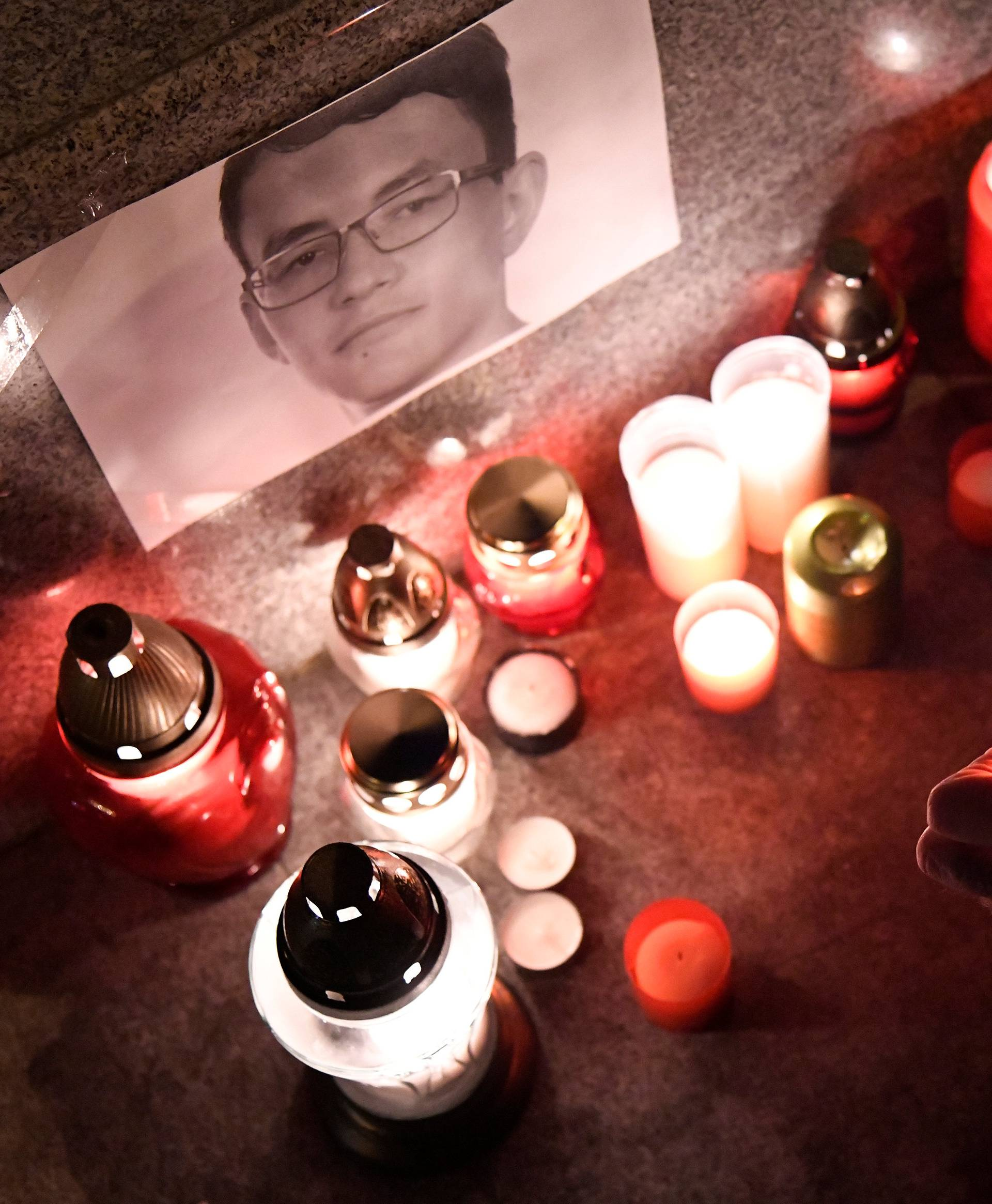 A journalist lights a candle in memory of murdered investigative journalist Jan Kuciak, in Trencin