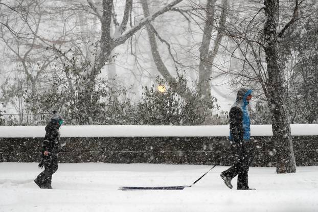 Man pulls sled in heavy falling snow in Manhattan during winter storm in New York